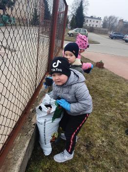 Na pierwszym planie, chłopiec nabiera ziemię do doniczki. Na drugim  planie dwoje dzieci  czeka w kolejce do pobrania ziemi.
